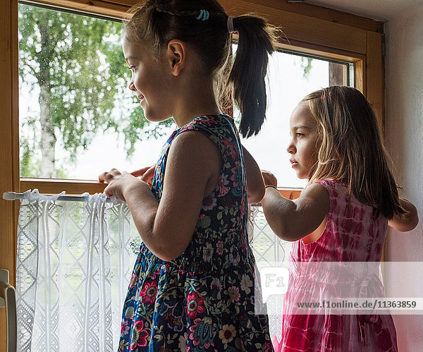 Mädchen  die aus dem Fenster schauen