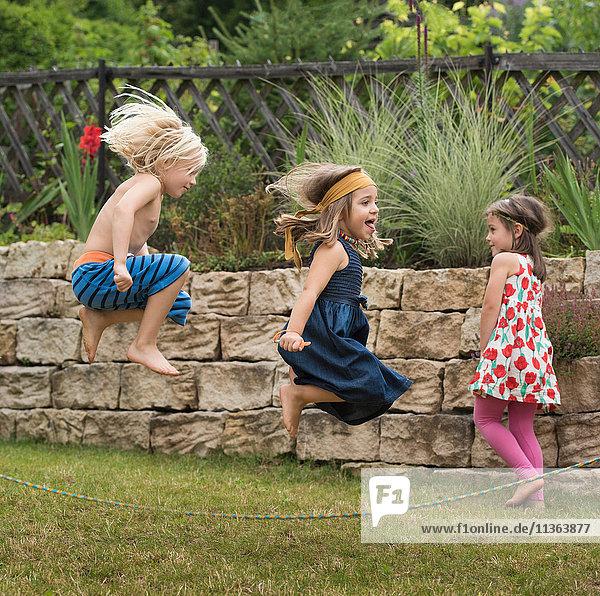 Kinder spielen mit Springseilspringen in der Luft