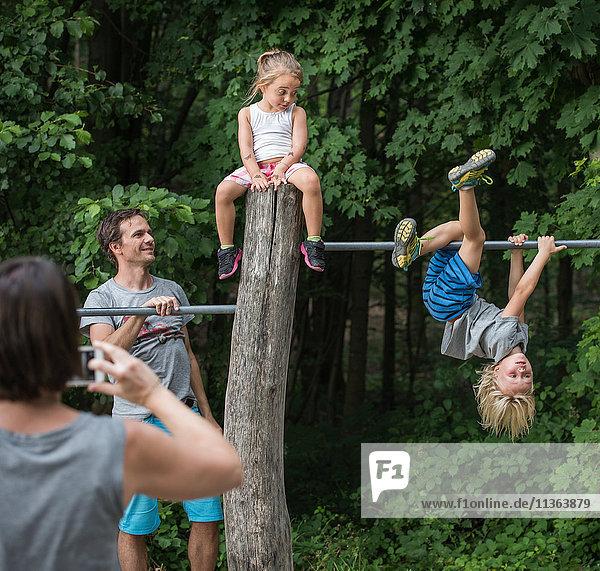 Mutter fotografiert spielende Kinder auf Affenstange