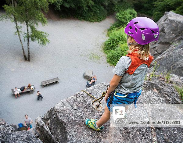 Junge mit Kletterhelm auf Fels stehend mit Blick nach unten