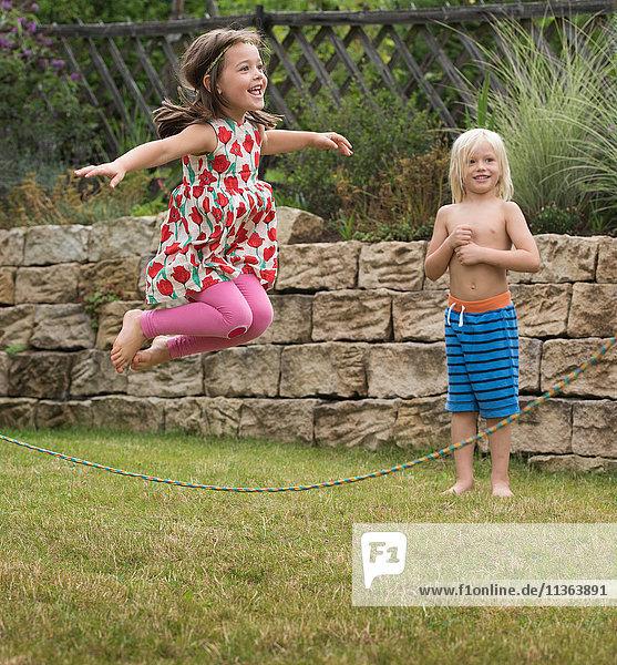 Mädchen spielt mit Springseilspringen in der Luft