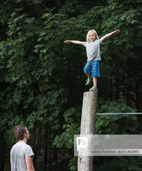 Junge auf einem Bein  Arme offen  auf Stange balancierend