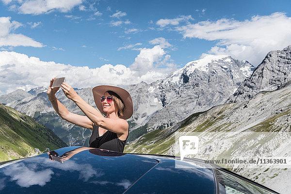 Woman taking selfie in front of mountains  Passo di Stelvio  Stelvio  Italy