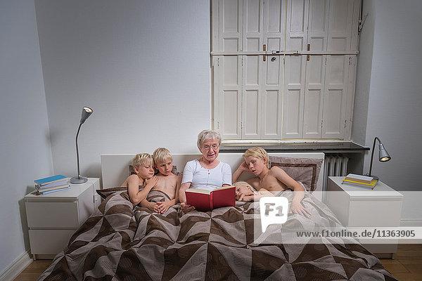 Großmutter im Bett mit Enkel liest Geschichtenbuch