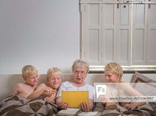 Großmutter im Bett mit Enkelkindern mit digitalem Tablett