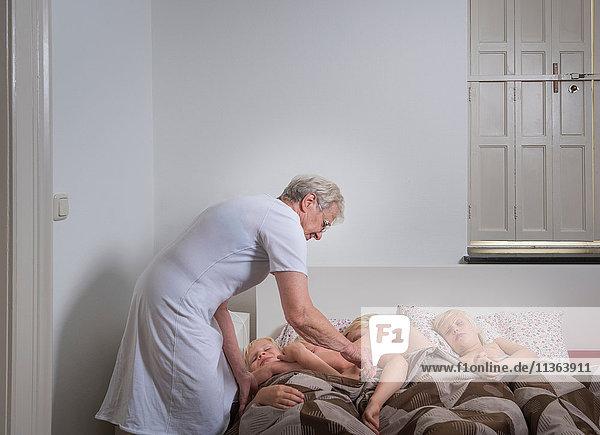 Großmutter setzt Enkel ins Bett