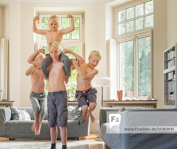 Junge im Wohnzimmer trägt Bruder auf den Schultern