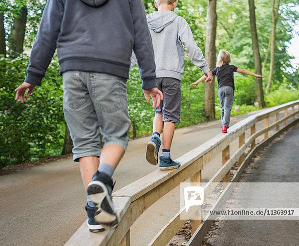 Rückansicht von Jungen  die auf einem Handlauf balancieren