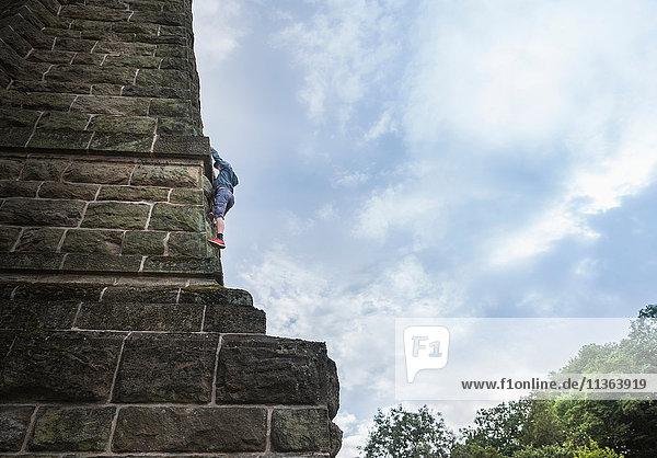 Niedrigwinkelansicht eines Jungen  der an einer Steinwand klettert