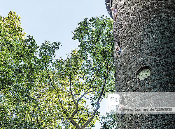 Jungen  die sich aus steinernen Turmfenstern lehnen