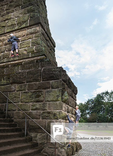 Jungen klettern an Steinwand