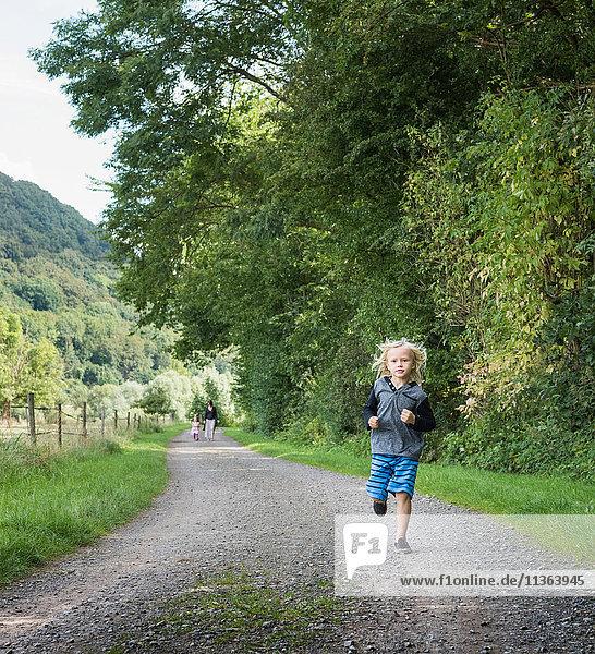 Junge mit Familie auf Landstraße laufend  Porta Westfalica  Nordrhein-Westfalen  Deutschland