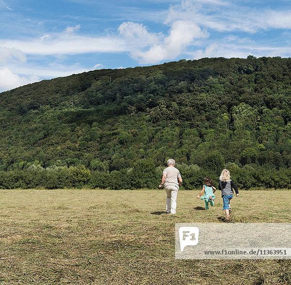 Rückansicht einer Großmutter mit Enkelkindern  die über das Feld joggen  Porta Westfalica  Nordrhein-Westfalen  Deutschland