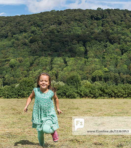 Mädchen läuft im Feld und schaut lächelnd in die Kamera  Porta Westfalica  Nordrhein-Westfalen  Deutschland