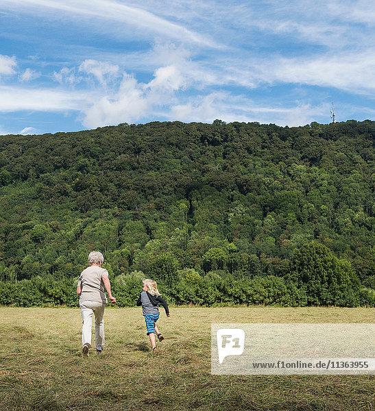 Rückansicht der Großmutter mit dem über das Feld joggenden Enkel  Porta Westfalica  Nordrhein-Westfalen  Deutschland
