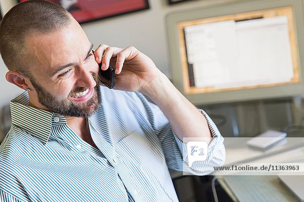 Mid adult man talking on smartphone  working at home