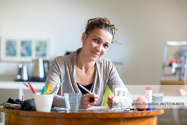 Porträt einer reifen Frau  die am Schreibtisch sitzt und einen Stift hält