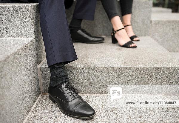 Beschnittener Blick auf die Füße von Geschäftsleuten
