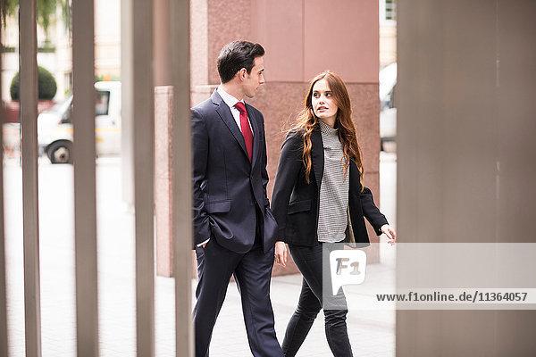 Geschäftsleute  die in der Stadt spazieren gehen und reden.