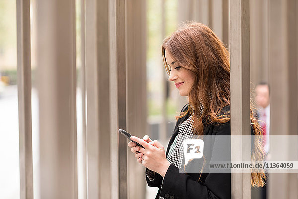 Geschäftsfrau in der Stadt sucht Smartphone