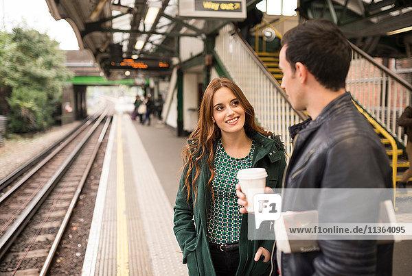 Paar auf dem Bahnsteig von Angesicht zu Angesicht lächelnd