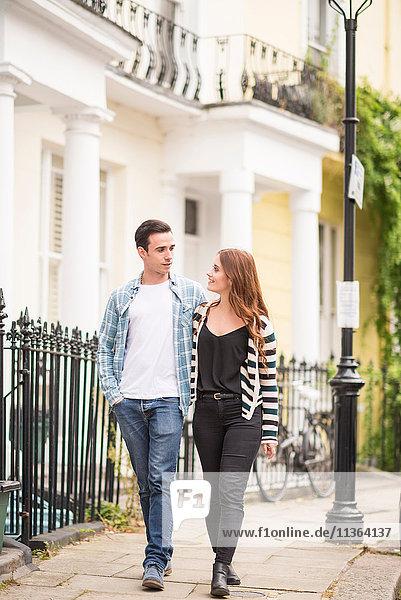 Ein Paar geht von Angesicht zu Angesicht lächelnd auf der Straße.