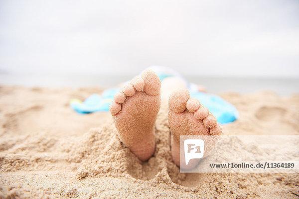Kind am Sandstrand liegend  Blick von den Füßen