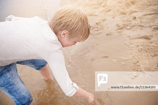 Junge zeichnet im Sand