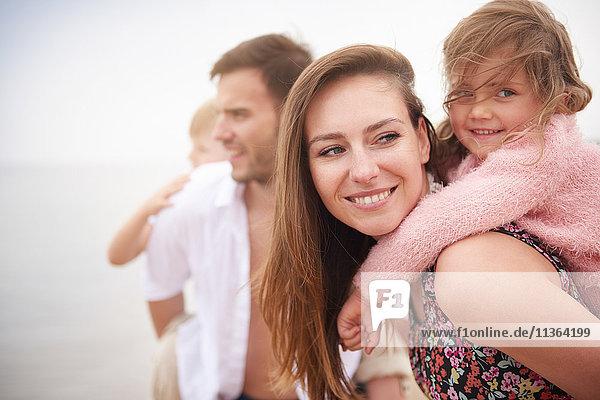 Eltern geben Kindern Huckepack am Strand