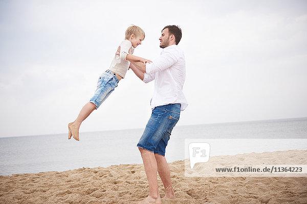 Vater schwingt Sohn am Strand