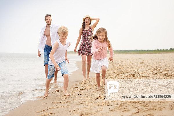 Familie läuft am Sandstrand entlang