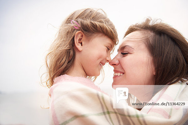 Happy mother and daughter wrapped in blanket  rubbing noses