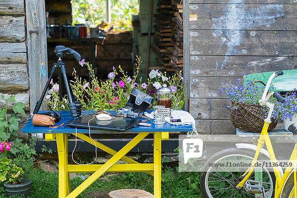 Camera equipment and laptop on table in garden