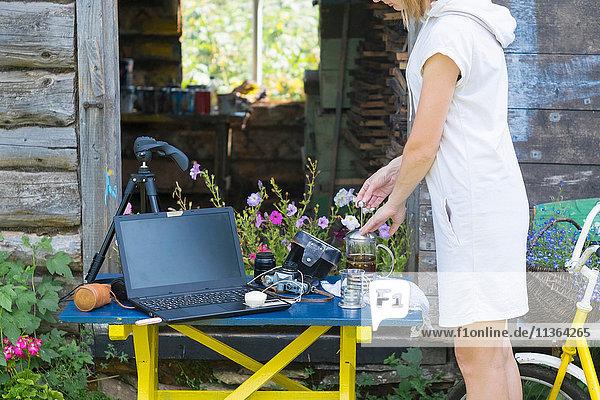 Frau benutzt Cafetiere im Freien  Kameraausrüstung und Laptop auf dem Tisch neben dem Cafetiere  Mittelteil