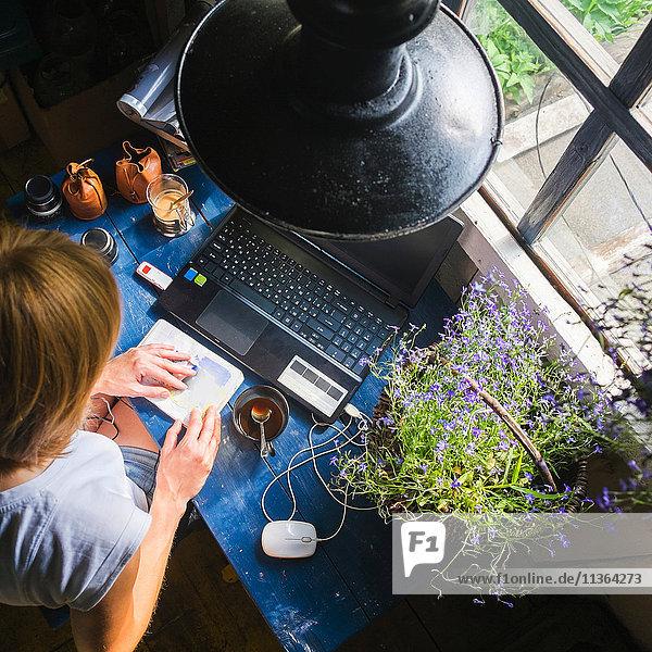 Mittelgroße erwachsene Frau am Schreibtisch sitzend  mit Laptop  Blick auf Notebook  Draufsicht