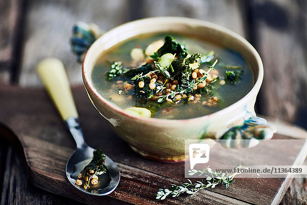 Bowl of broth on wooden cutting board