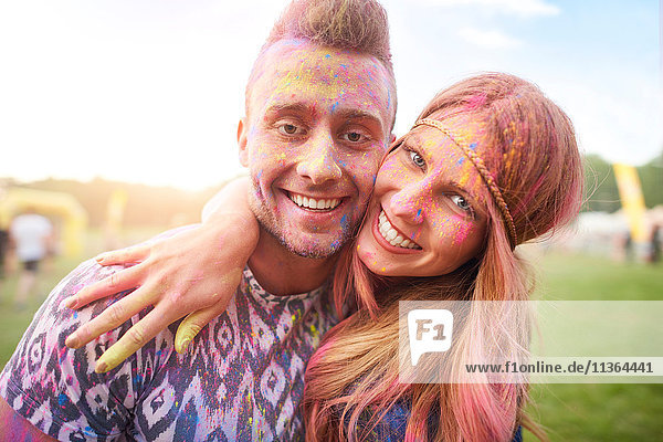 Two friends at festival  covered in colourful powder paint