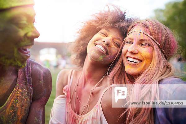 Group of friends at festival  covered in colourful powder paint