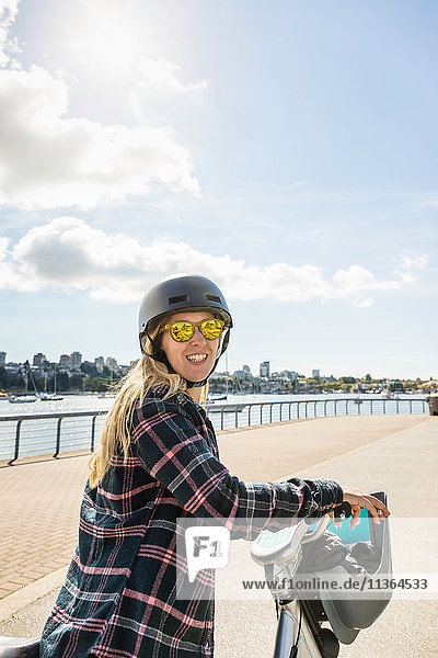 Portrait of woman on bicycle at waterfront  Vancouver  Canada