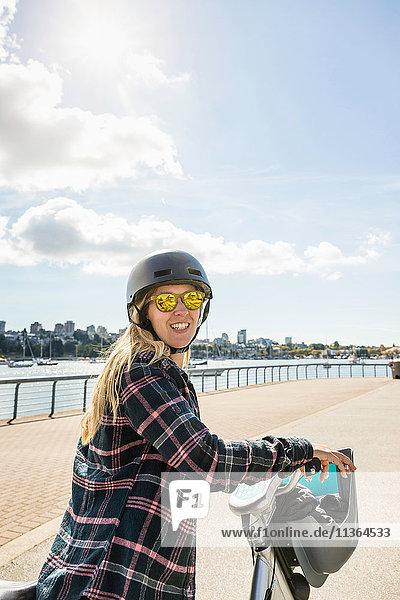 Porträt einer Frau auf dem Fahrrad am Wasser  Vancouver  Kanada