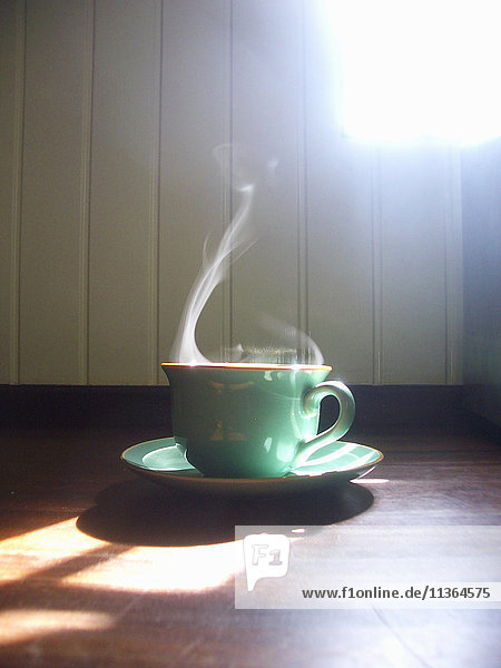 Steaming coffee in green cup and saucer on table