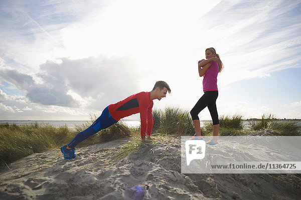 Couple on sand dune doing stretching exercises