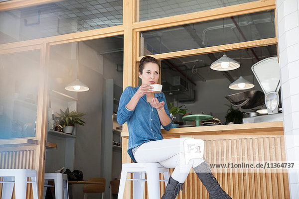 Young woman sitting at bar in cafe  holding coffee cup