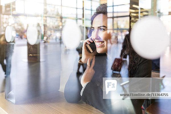 Mittlere erwachsene Frau  sitzend im Café  mit Smartphone