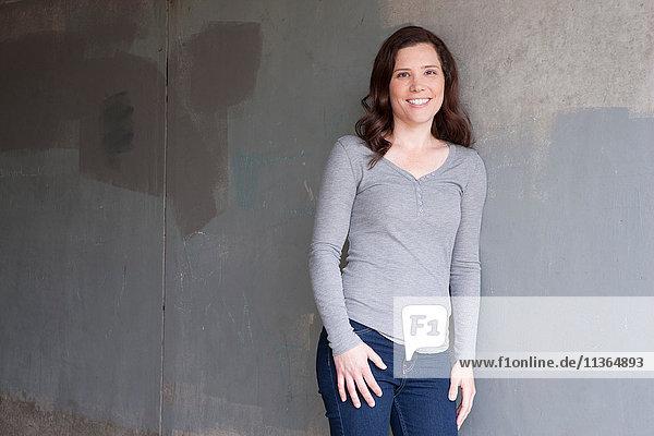 Porträt einer mittelgroßen erwachsenen Frau  die lächelnd an der Wand lehnt