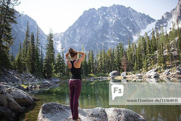 Junge Frau steht auf einem Felsen am See und schaut auf die Aussicht  Die Verzauberungen  Alpine Lakes Wilderness  Washington  USA