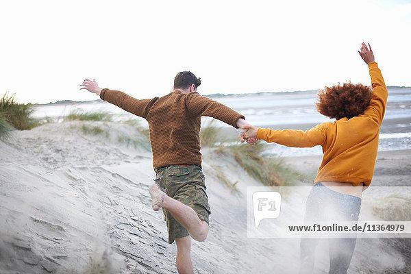 Ehepaar läuft Sanddünen hinunter zum Strand