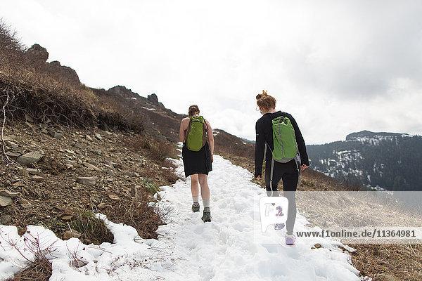 Two young women hiking along mountain-side  rear view  Silver Star Mountain  Washington  USA