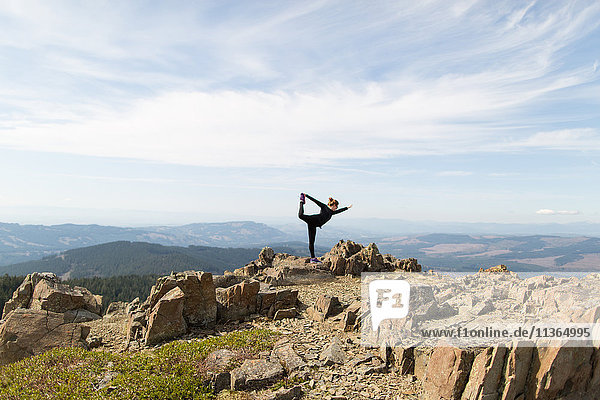 Young woman standing on rock  in yoga position  Silver Star Mountain  Washington  USA
