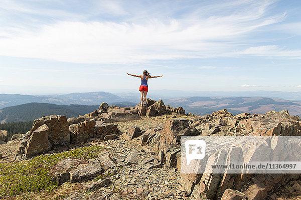 Junge Frau steht auf Fels und schaut auf Aussicht  Silver Star Mountain  Washington  USA